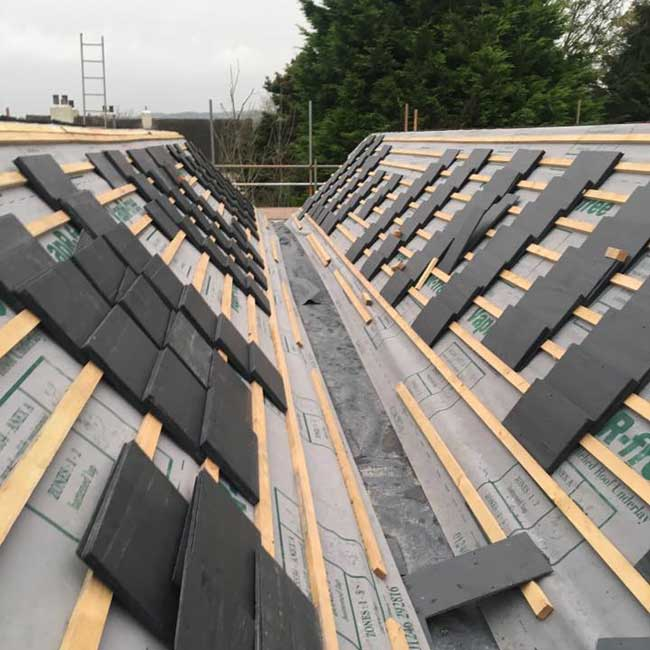 Natural slate tiles stacked on a new roof ready for installation